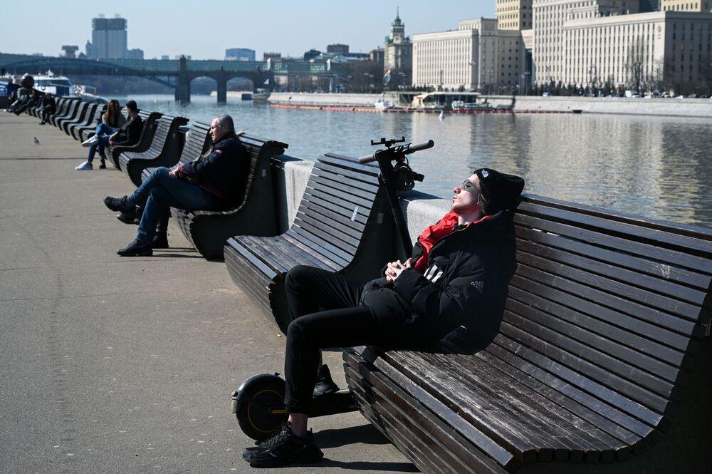 أشخاص يجلسون على مقاعد على ضفة نهر موسكو، روسيا 11 أبريل 2021