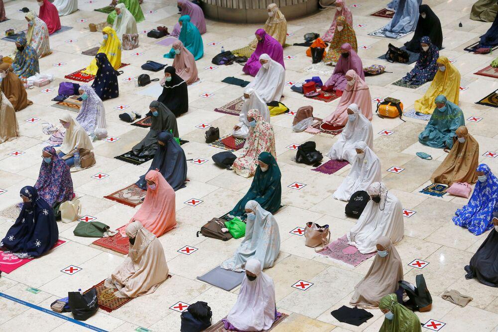 نساء ترتدي كمامات واقية وتتابعد اجتماعيا خلال صلاة التراويح الأولى في رمضان هذا العام في مسجد استقلال، إندونيسيا 12 أبريل 2021