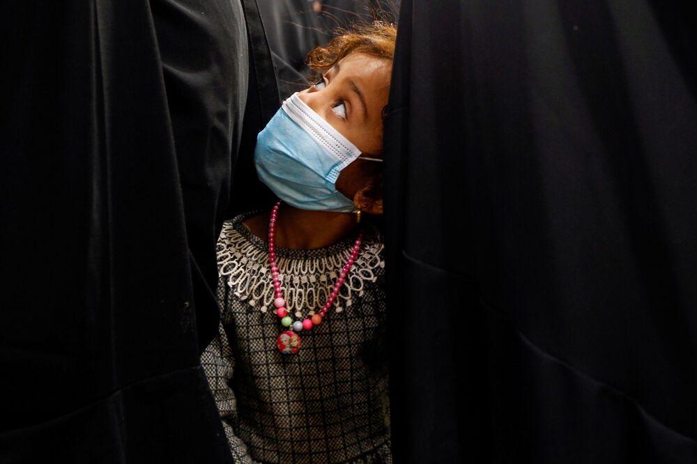 طفلة ترتدي كمامة واقية تف برفقة والدتها لاستلام نصيبهما من الطعام من جمعية خيرية في النجف قبل بدء شهر رمضان، العراق 12 أبريل 2021