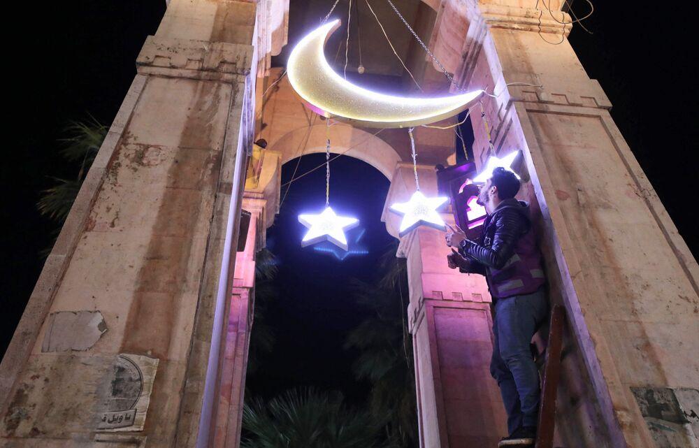 شاب يقوم بتزيين ميدان الساعة في إدلب بمناسبة حلول شهر رمضان، سوريا 12 أبريل 2021