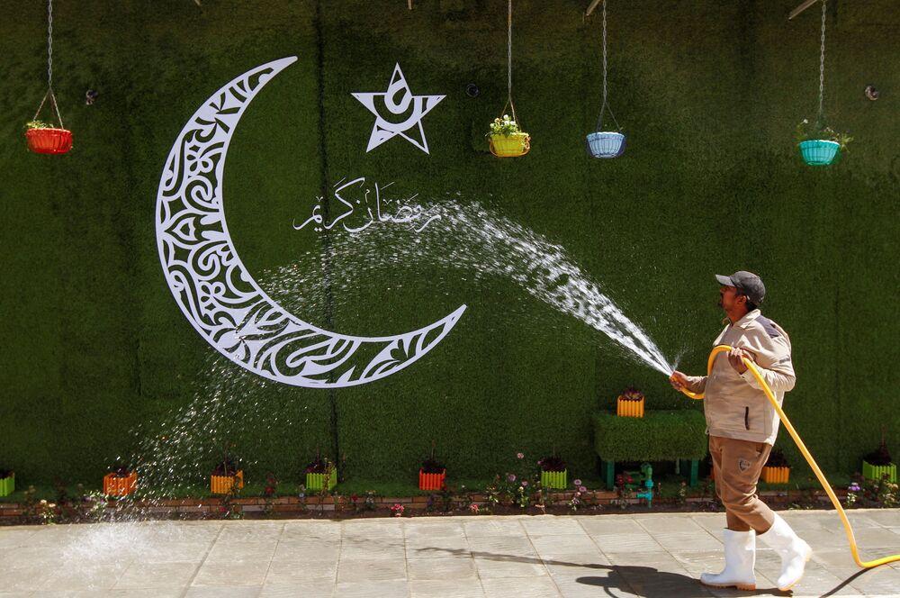 موظف يقون بتنظيف شارع في مدينة النجف بمناسبة حلول شهر رمضان، العراق 12 أبريل 2021