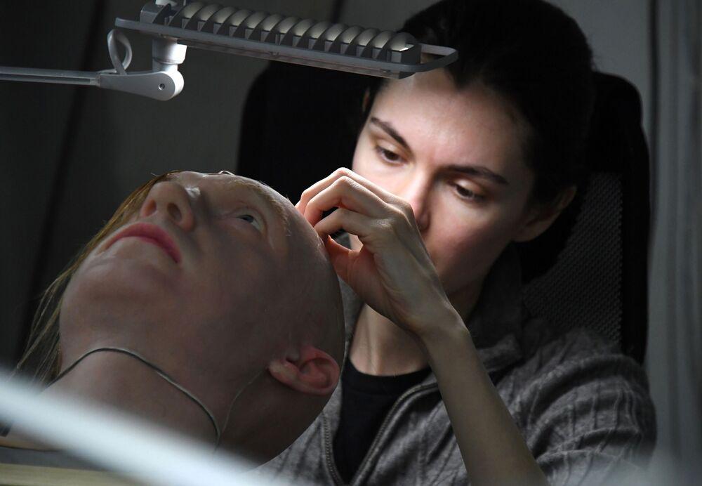 ألكسندرا تشيغودايفا، نائبة مدير شركة بروموبود لتصنيع الروبوتات، تقوم بتركيب الشعر لرجل آلي في فرع الشركة لنمذجة الروبوتات البشرية في أقصى شرق مدينة فلاديفوستوك، روسيا، 15 مارس 2021
