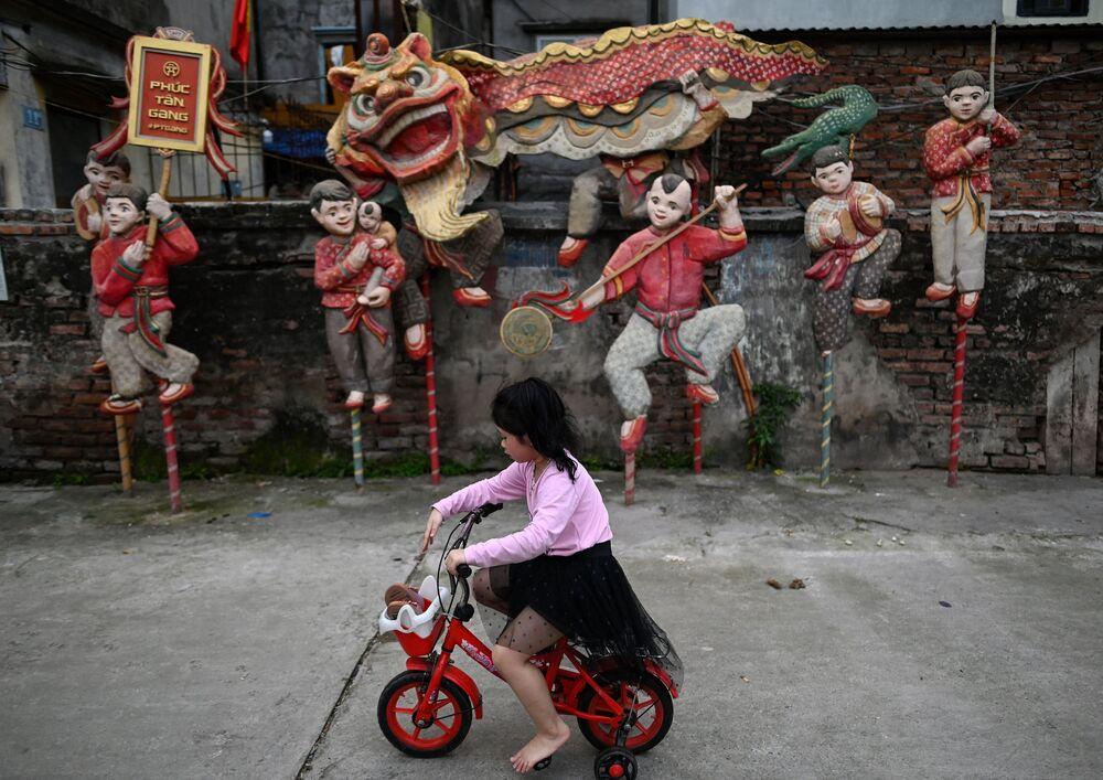 فتاة صغيرة تركب دراجتها على خلفية لوحة مركبة بعنوان رقصة الأسد للفنان نجوين شوان لام، في مساحة فوك تان للفنون العامة في هانوي، فيتنام 14 أبريل 2021