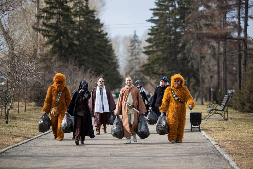 متطوعون يرتدون زي شخصيات من فيلم حرب النجوم، يسيرون خلال فعالية لتنظيف الشوارع بمناسبة الذكرى الـ60 لأول رحلة فضاء مأهولة (أول رائد فضاء يوري غاغارين) في مدينة إيركوتسك، روسيا في 12 أبريل 2021.