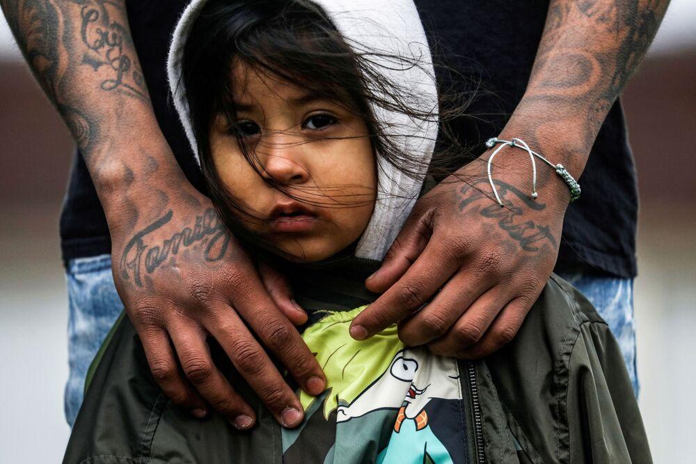 يضع خوسيه تشافيز، المقيم في مركز بروكلين، ذراعيه حول ابنته كاتليا شافيز، 3 سنوات، أثناء استماعهم إلى المتحدثين خلال احتجاج خارج قسم شرطة مركز بروكلين، بعد أيام من إطلاق النار على داونتي رايت وقتله على يد ضابط شرطة في مركز بروكلين، مينيسوتا، الولايات المتحدة 13 أبريل 2021