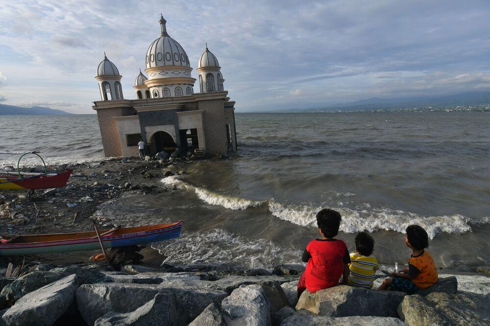أطفال يجلسون بالقرب من مسجد على الشاطئ أثناء انتظارهم آذان المغربل للإفطار، خلال شهر رمضان المبارك وسط جائحة فيروس كورونا (كوفيد-19) في بالو، مقاطعة سولاويزي الوسطى، إندونيسيا، 13 أبريل 2021