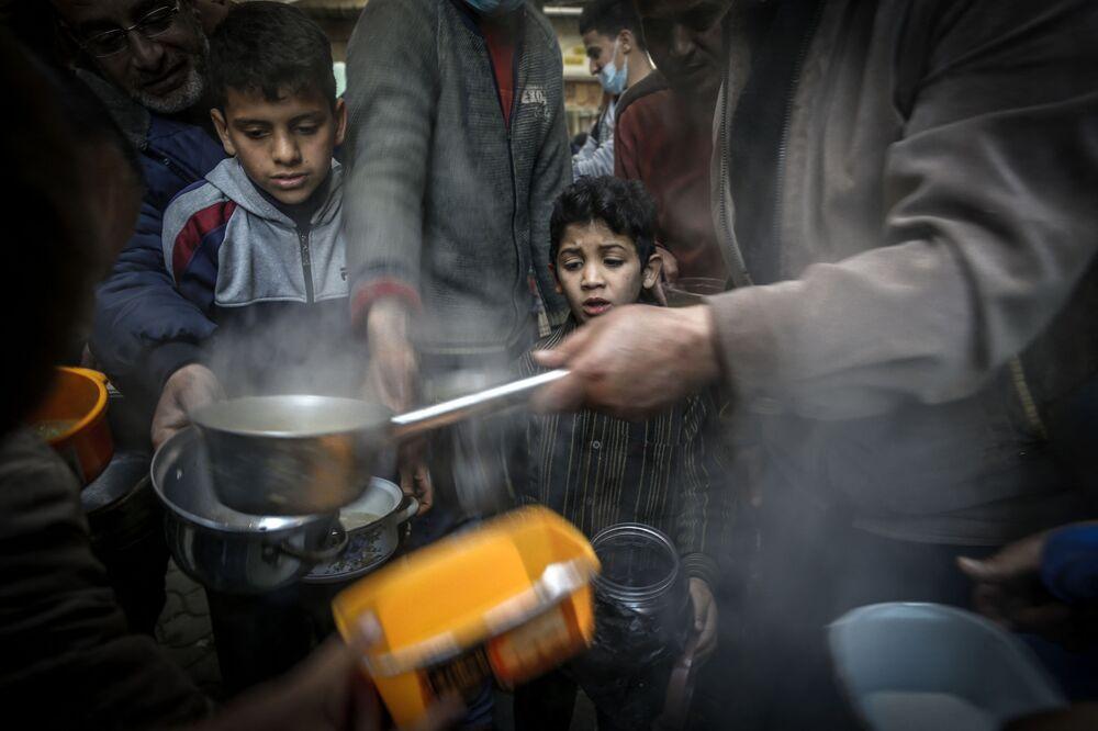 صبي ينتظر دوره للحصول على وجبة إفطار، خلال فعالية خيرية لمساعدة المحتاجين والفقراء في شهر رمضان، مدينة غزة، قطاع غزة، فلسطين 14 أبريل 2021