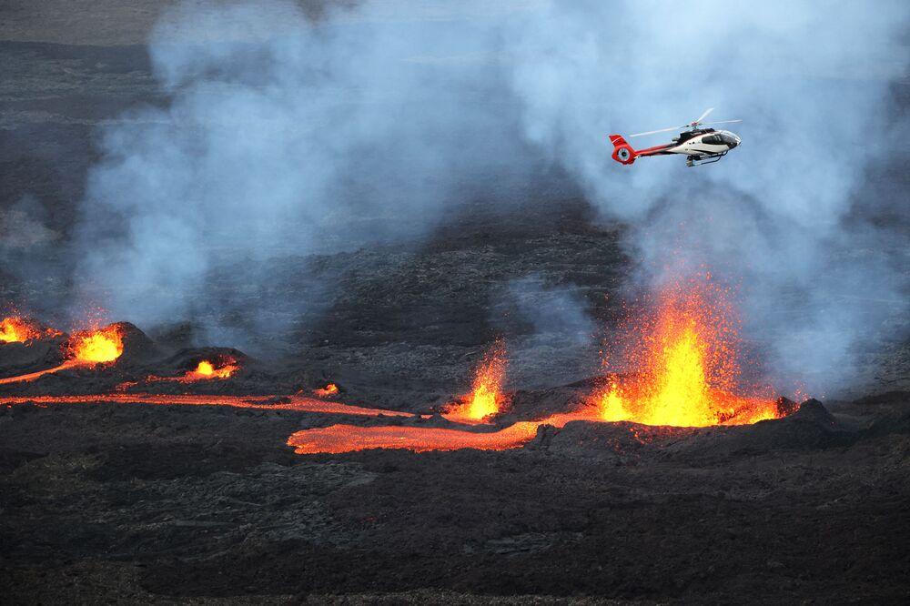 تُظهر هذه الصورة التي التقطت في 10 أبريل 2021 طائرة هليكوبتر تحلق فوق الحمم البركانية من بركان بيتون دي لا فورنيز، على الجانب الجنوبي من البركان، في جزيرة ريونيون الفرنسية في المحيط الهندي.