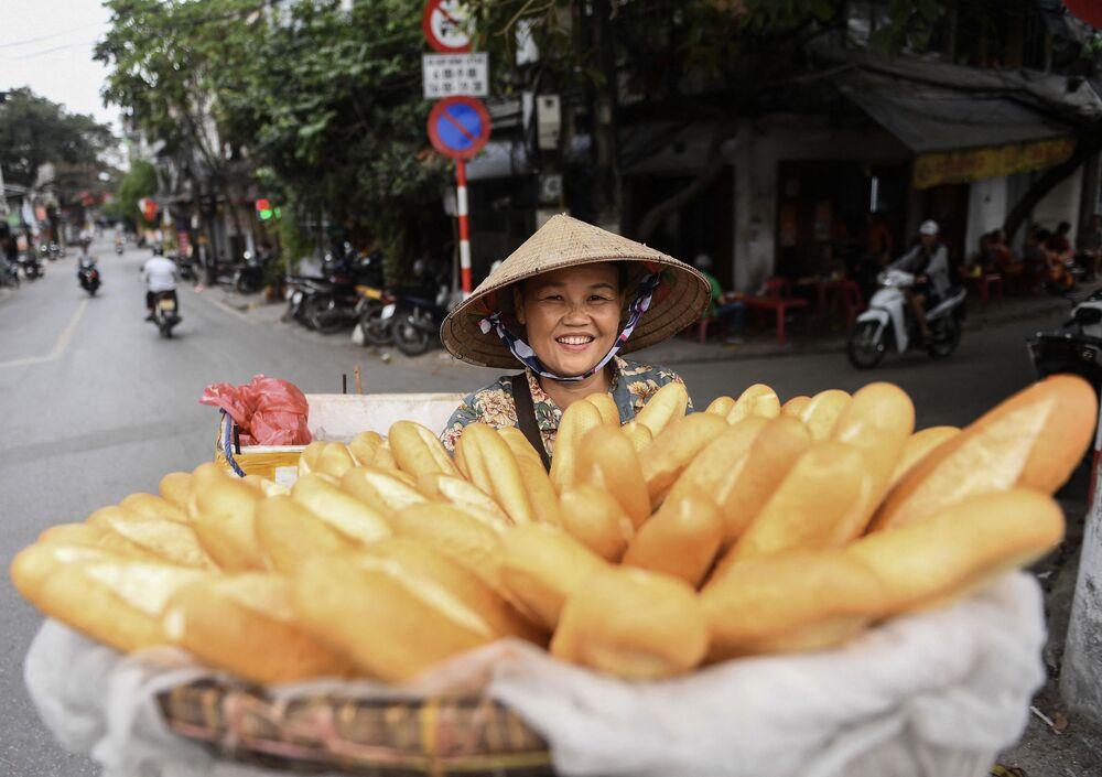 بائعة متجولة تحمل خبز من نوع باغيت للبيع على دراجتها في إحدى شوارع مدينة هانوي، فيتنام 14 أبريل 2021