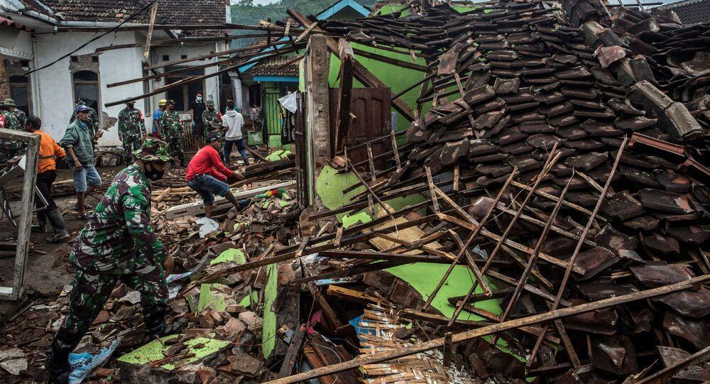 جنود ومواطنون إندونيسيون يفحصون المنازل المتضررة في مالانغ،11 أبريل 2021  بعد يوم من وقوع زلزال بلغت قوته 6.0 درجات قبالة ساحل جزيرة جاوا الرئيسية في إندونيسيا