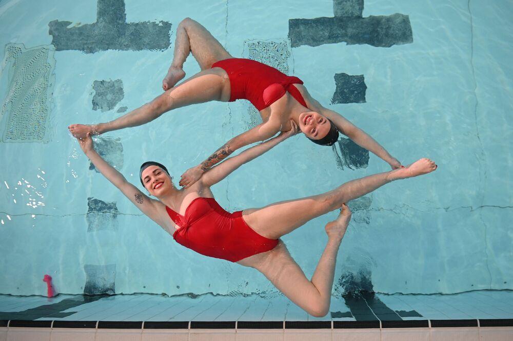 أعضاء فريق أكواباتيكس، وهو فريق سباحة متزامن يتدرب في مركز الترفيه كليسولد في شمال لندن، حيث تم تخفيف قيود المفروضة بسبب كورونا في جميع أنحاء البلاد بعد الإغلاق العام الثالث لإنجلترا في 12 أبريل 2021