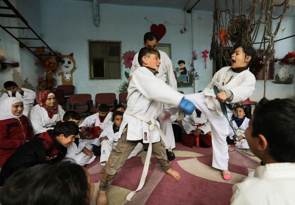 شبان يمارسون فنون القتال أثناء تدريب في مدرسة بقرية الجينة، سوريا، 11 أبريل2021