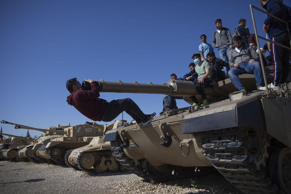 طلاب يصعدون على دبابة في إطار فعاليات الاحتفال بالذكرى السنوية لإحياء ذكرى الجنود القتلى وضحايا الإرهاب، في موقع نصب سلاح المدرعات في اللطرون، إسرائيل، 14 أبريل 2021