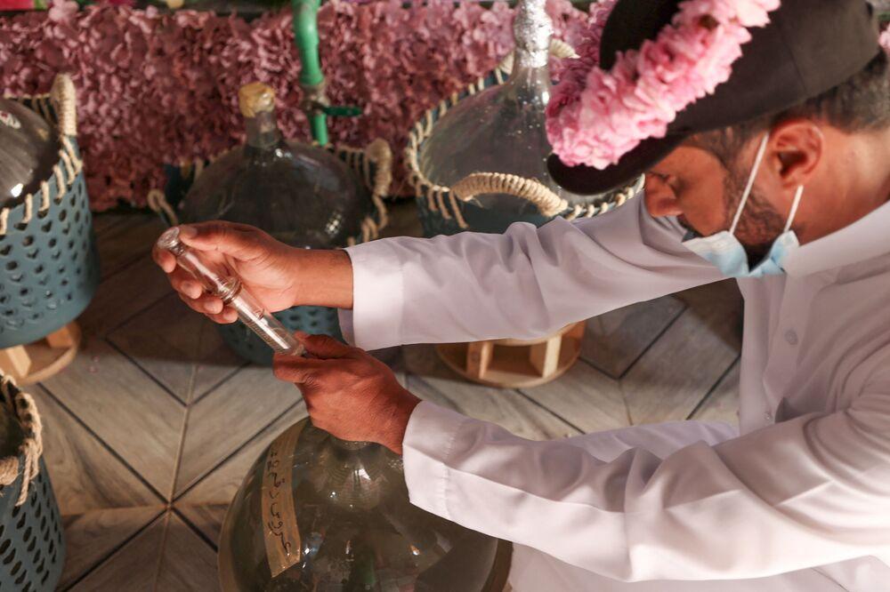 عامل بمزرعة بن سلمان يستخرج زيت الورد من سطح ماء الورد المقطر في مدينة الطائف غرب السعودية، 11 أبريل 2021