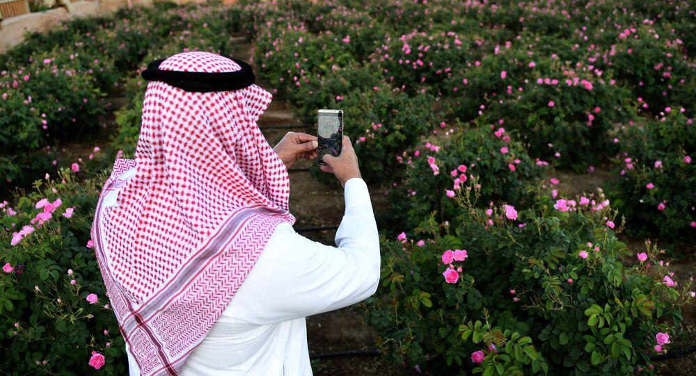 رجل سعودي يلتقط صورة للورود في مزرعة بن سلمان في مدينة الطائف غرب السعودية 13 مارس2021