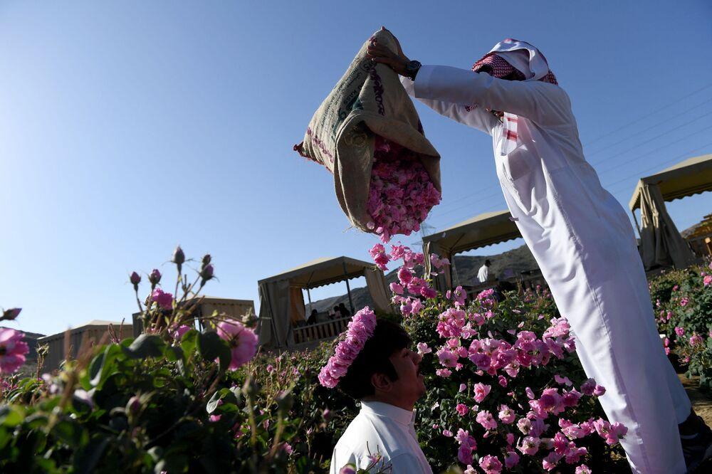 سلمان، أحد أفراد عائلة بن سلمان، يلقي بالورود في الهواء في مزرعة العائلة في مدينة الطائف السعودية، 13 مارس 2021