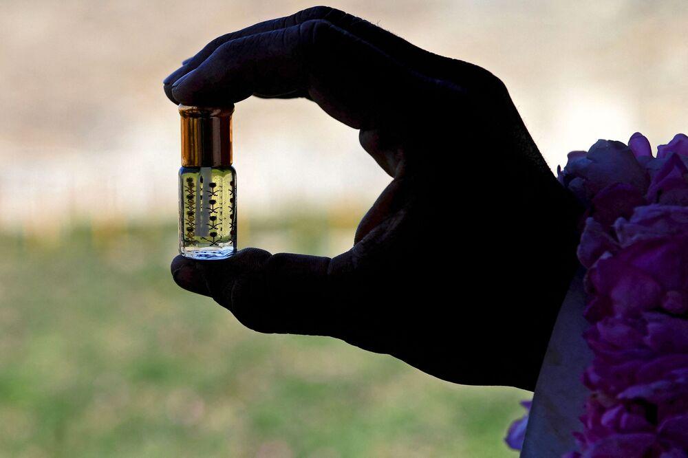 عامل يعرض زجاجة من زيت ورد الطائف المقطر من مزرعة بن سلمان في مدينة الطائف السعودية في 13 مارس 2021