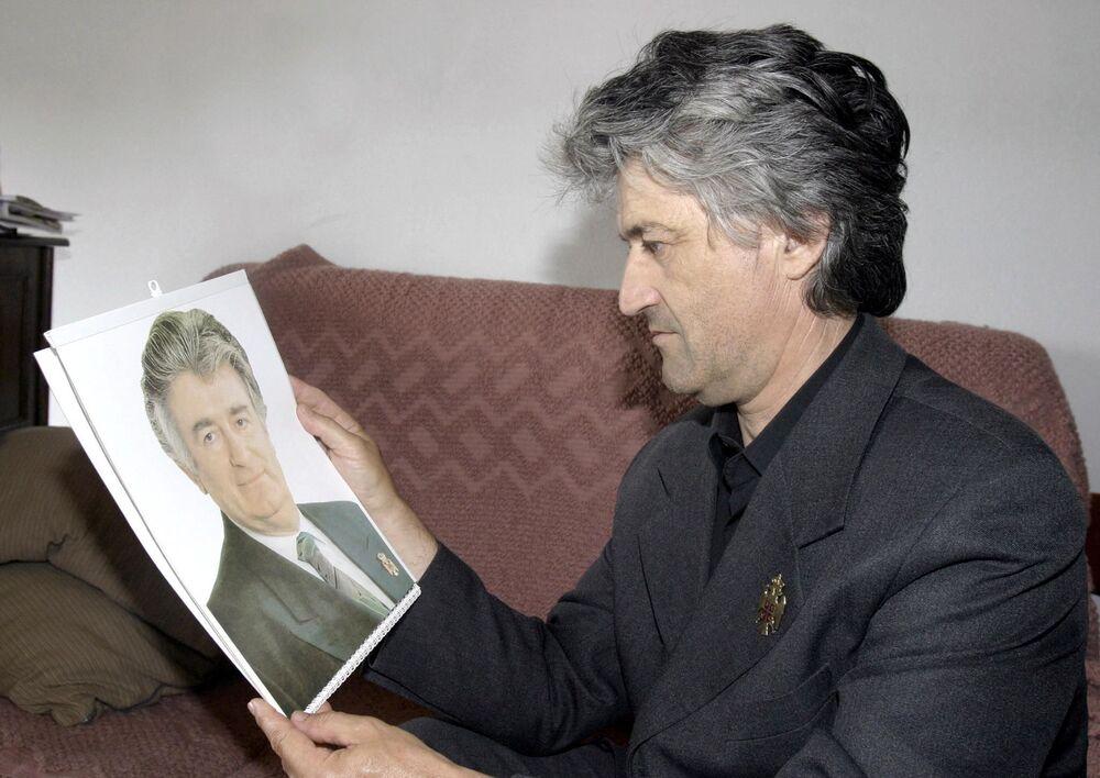 رجل يدعى بيتر سيكيتش ينظر إلى صورة شبيهه السياسي الصربي والرجل الملاحق من المحكمة الجنائية الدولية رادوفان كاراديتش، 2004