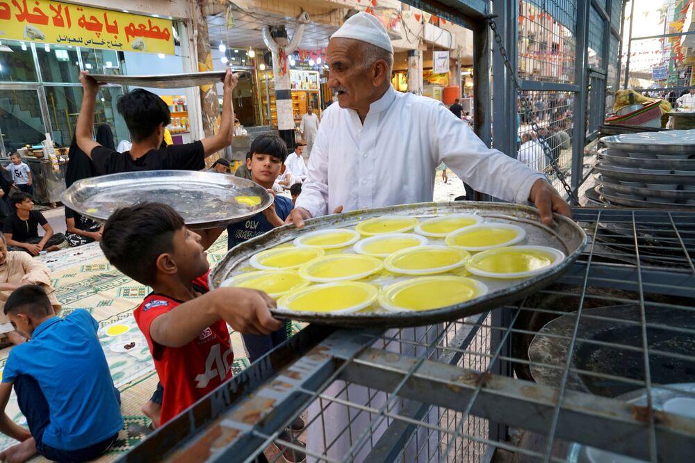 العراقيون يحملون الأطباق بينما يتجمع الناس لتناول الإفطار خلال إفطار جماعي مجاني في أحد الشوارع بمناسبة شهر رمضان في النجف، العراق، 18 أبريل 2021