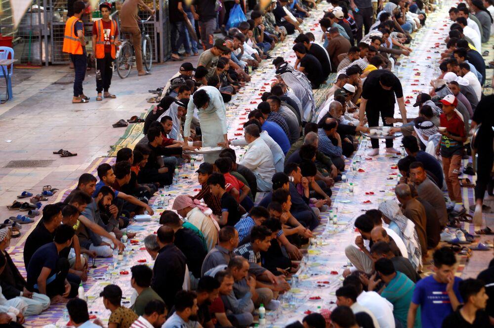 إفطار جماعي مجاني في أحد الشوارع بمناسبة شهر رمضان في النجف، العراق، 18 أبريل 2021