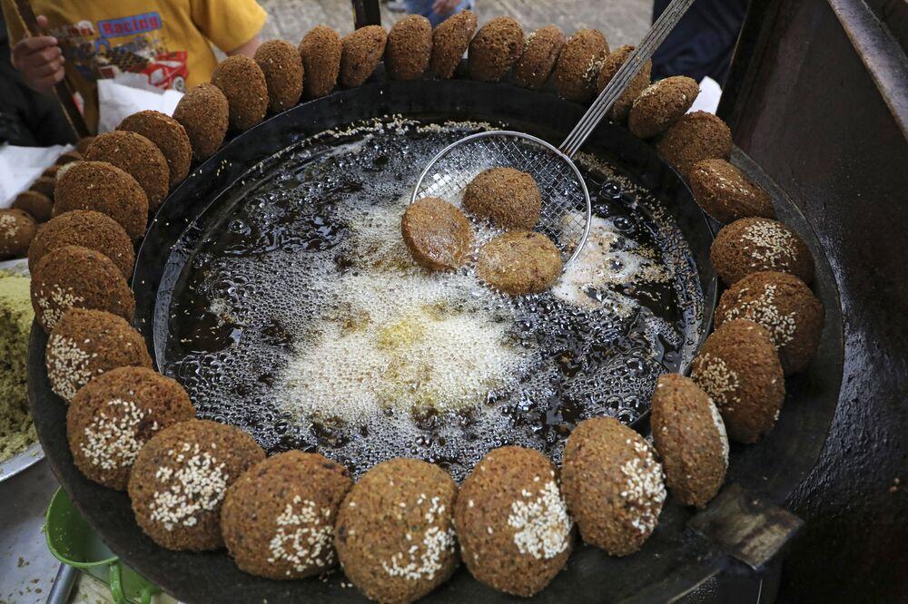 بائع فلسطيني يعد الفلافل قبل الإفطار بقليل في مدينة الخليل، الضفة الغربية، فلسطين 18 أبريل 2021