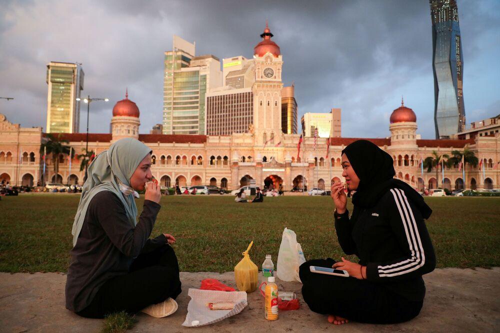 شابات يفطرن في ميدان الاستقلال، وسط اجراءات احترازية بسبب مرض فيروس كورونا (كوفيد-19) في كوالالمبور، ماليزيا، 20 أبريل 2021
