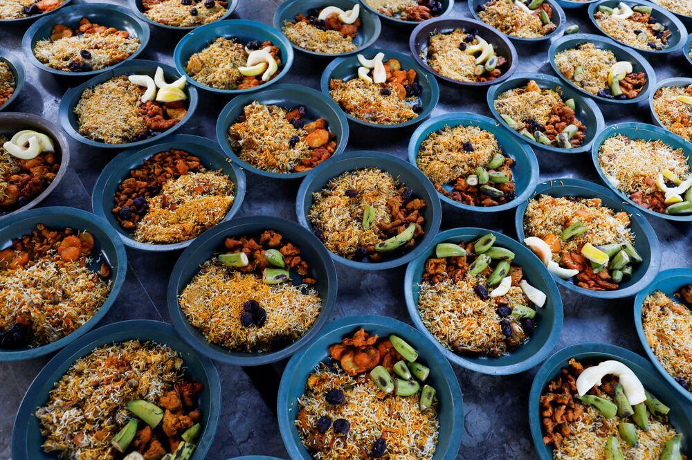 أواني من الأرز المطبوخ والفواكه جاهزة للتوزيع على الصائمين قبيل إفطار رمضان،  وسط اجراءات احترازية بسبب مرض فيروس كورونا (كوفيد-19) في كراتشي، باكستان، 17 أبريل 202