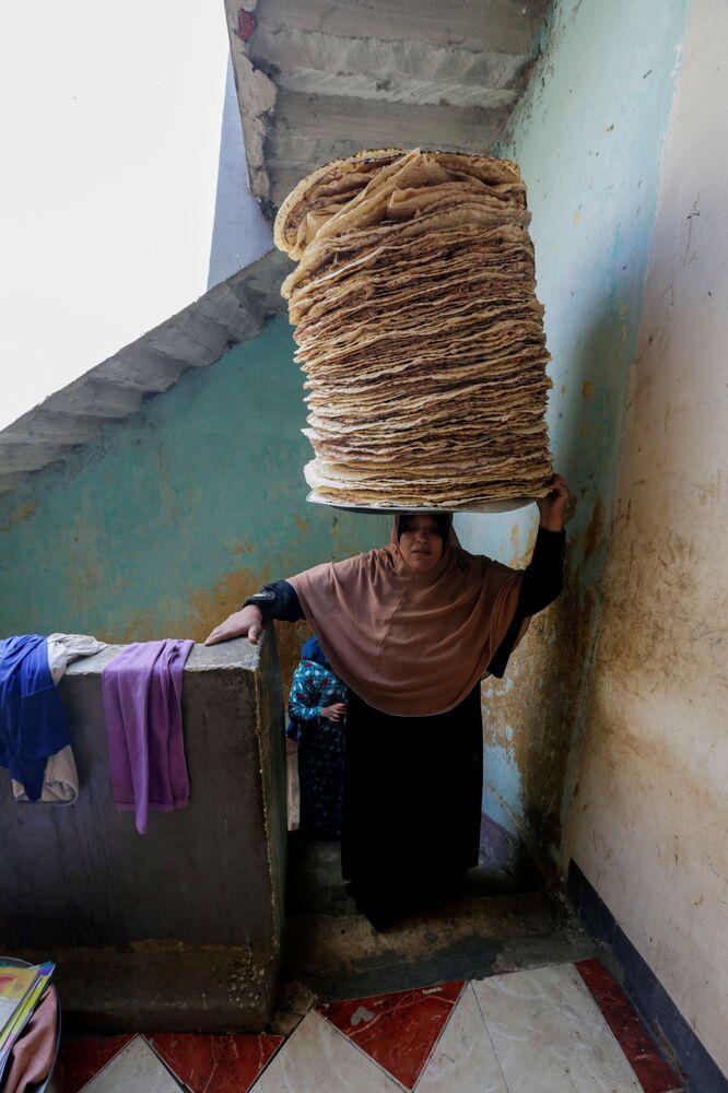 نور الصباح، 35 عامًا، تحمل الخبز على رأسها، تصعد اسلم منزلها، قبيل إفطار رمضان في بني سويف، مصر، 10 أبريل 2021