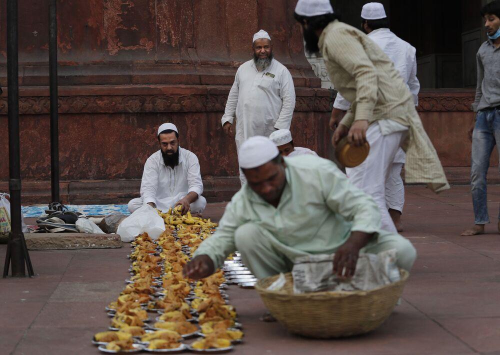 يقوم المسلمون بإعداد أطباق مع وجبات خفيفة لتوزيعها على الإفطار في اليوم الأول من شهر رمضان في المسجد الجامع في نيودلهي، الهند 14 أبريل 2021
