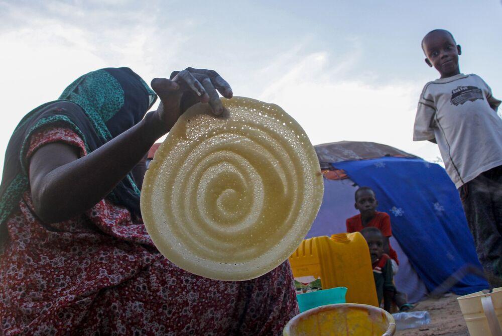 امرأة صومالية تصنع الفطائر لعائلتها في رمضان، في مخيم للنازحين في حي دار السلام بالعاصمة مقديشو، الصومال، 16 أبريل 2021