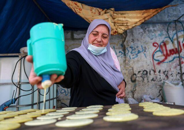 الفلسطينية مريم صالحة تصنع القطايف، حلويات تقليدية في شهر رمضان في دير البلح وسط قطاع غزة، فلسطين 19 أبريل 2021