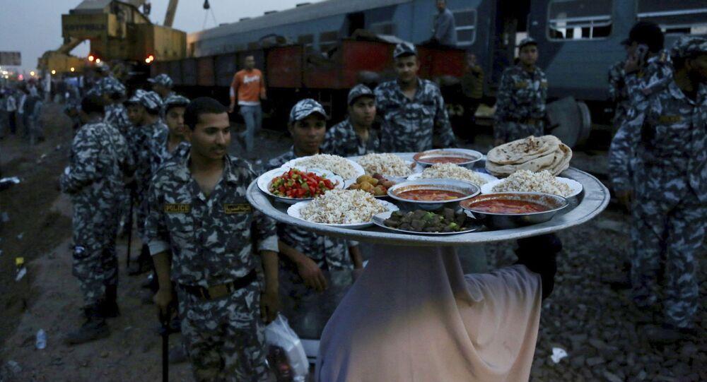 امرأة تجلب الطعام لقوات الأمن لتناول إفطار رمضان، في موقع قطار ركاب خرج عن مساره مما أدى إلى إصابة حوالي 100 شخص بالقرب من بنها بمحافظة القليوبية، مصر، 18 أبريل 2021.