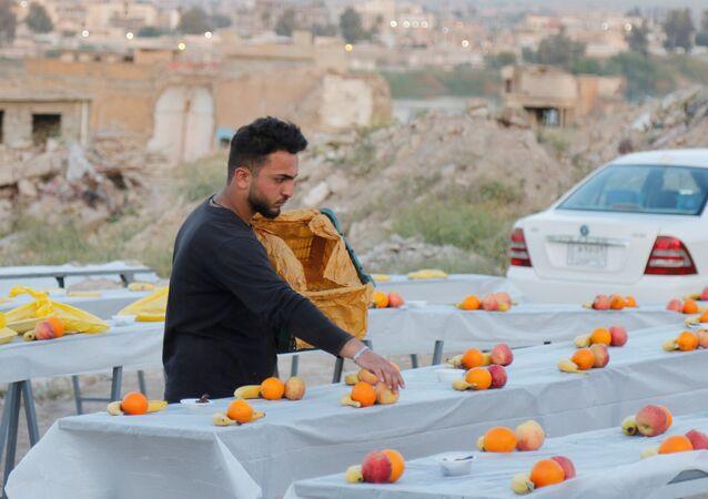 شاب يعد الطعام لوجبات الإفطار ويضع الفواكه على طاولة إفطار رمضان في الموصل، العراق، 15 أبريل 2021