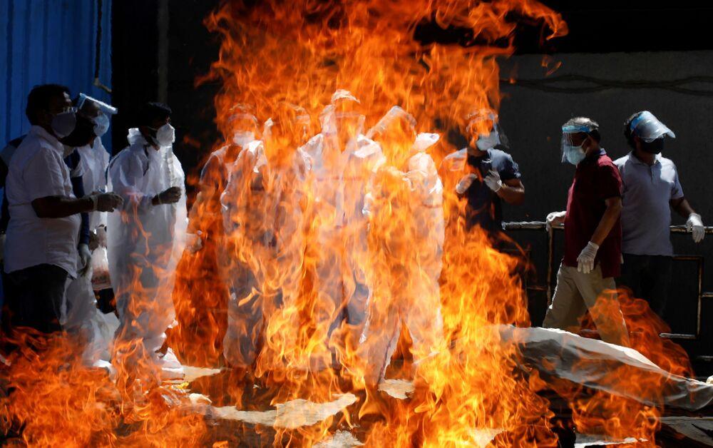 أقارب يرتدون أزياء الحماية الخاصة لحضور جنازة رجل، توفي إثر مضاعفات مرض كوفيد-19، في نيودلهي، الهند 21 أبريل 2021