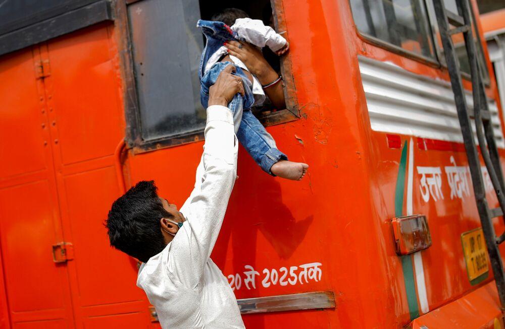 عامل مهاجر يمرر ابنه من خلال نافذة حافلة عمومية للعودة إلى القرية، بعد إعلان الحكومة الهندية عن إغلاق عام لمدة 6 أيام في كافة البلاد، وسط تصاعد حالات الإصابة بمرض كوفيد-19 في غازي آباد، الهند 20 أبريل 2021