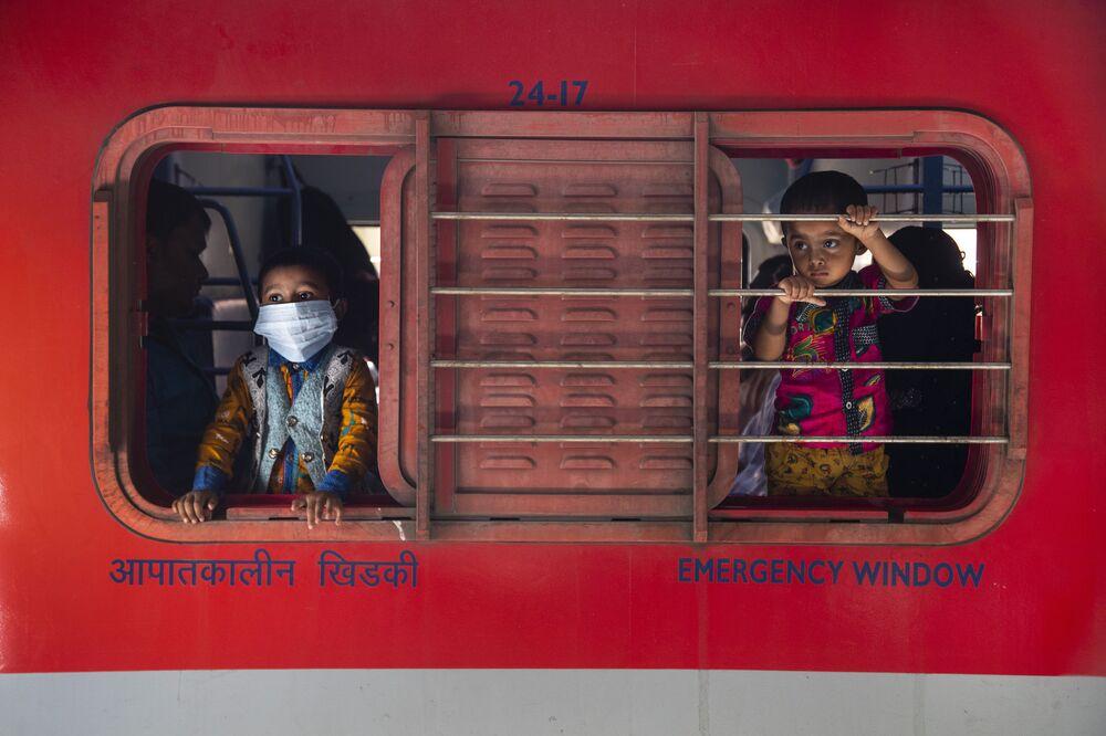 أطفال صغار ينظرون من نوافذ قطار على السكة الحديدية في غاهاتي، الهند 19 أبريل 2021. تحتل الهند الآن المركز الثاني من حيث حالات الإصابة بمرض كوفيد-19 بعد الولايات المتحدة