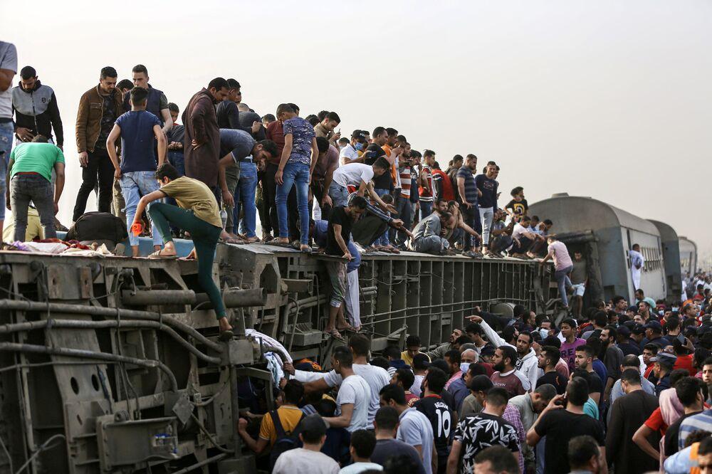 تجمع الناس حول قطار في موقع حادث سكة حديد في مدينة طوخ في محافظة القليوبية، وسط دلتا النيل في مصر، 18 أبريل 2021
