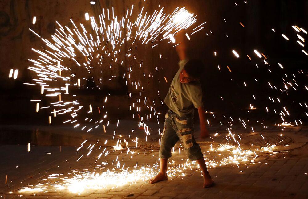 صبي يلعب بألعاب نارية احتفالا بحلول شهر رمضان ف يمدينة غزة، قطاع غزة، فلسطين 20 أبريل 2021
