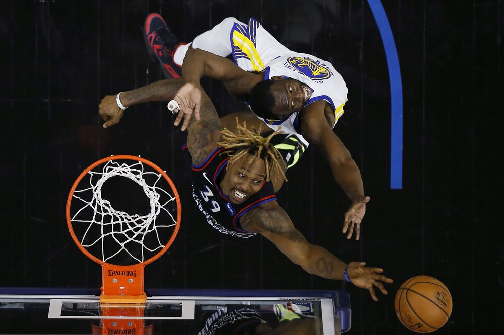 دوايت هوارد من فريق فيلادلفيا سفنتي سيكسرز، أسفل، ودرايموند رين من فريق غولدن ستايت ووريورز، أثناء ارتداد الكرة، خلال النصف الأول من مباراة كرة السلة في الدوري الأمريكي للمحترفين، في فيلادلفيا، 19 أبريل 2021