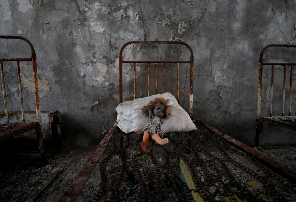 دمية قديمة وضعها زائر، شوهدت على سرير في روضة أطفال بالقرب من محطة تشيرنوبيل للطاقة النووية في مدينة بريبيات المهجورة (في ذكرى كارثة تشيرنوبيل)، أوكرانيا، 12 أبريل 2021