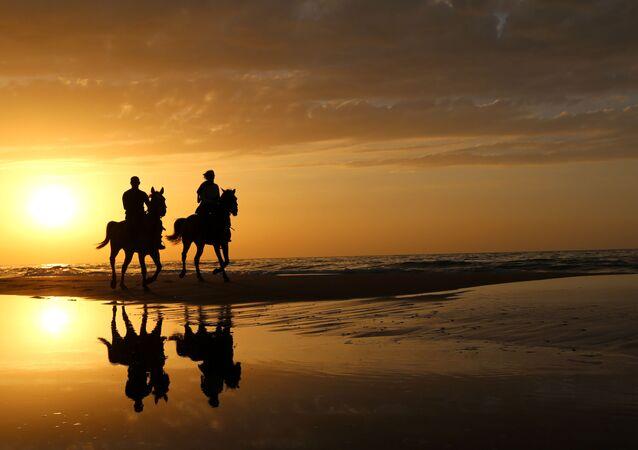 فلسطينيان يمتطيان الخيول مع غروب الشمس على شاطئ غزة