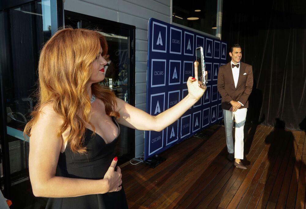 الممثلة الأمريكية إسلا فيشر تلتقط صورة سيلفي بينما يقف الممثل ساشا بارون كوهين للتصوير، يصلان السجادة الحمراء لحفل توزيع جوائز أوسكار بنسختها الـ93 في لوس أنجلوس، كاليفورنا، الولايات المتحدة 25 أبريل 2021