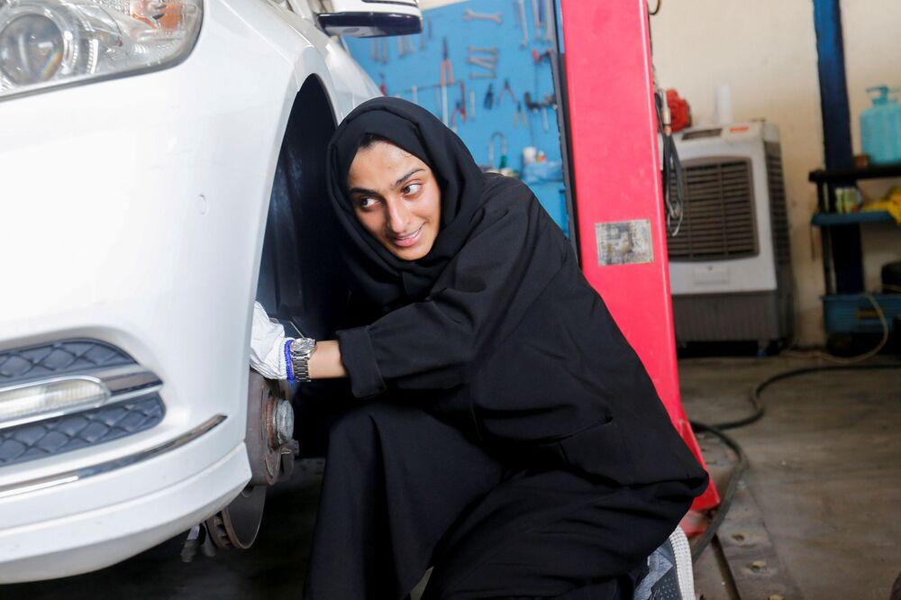الإماراتية هدى المطروشي، 36 عاماً، تملك وتدير كراجاً لتصليح السيارات، تقوم بتصليح عجلة السيارة في كراجها في الشارقة، الإمارات العربية المتحدة، 21 أبريل 2021