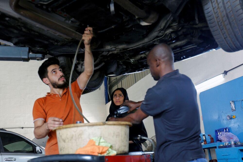 الإماراتية هدى المطروشي، 36 عاماً، مع فريق عملها أثناء تصليح سيارة في كراجها في الشارقة، الإمارات العربية المتحدة، 21 أبريل 2021