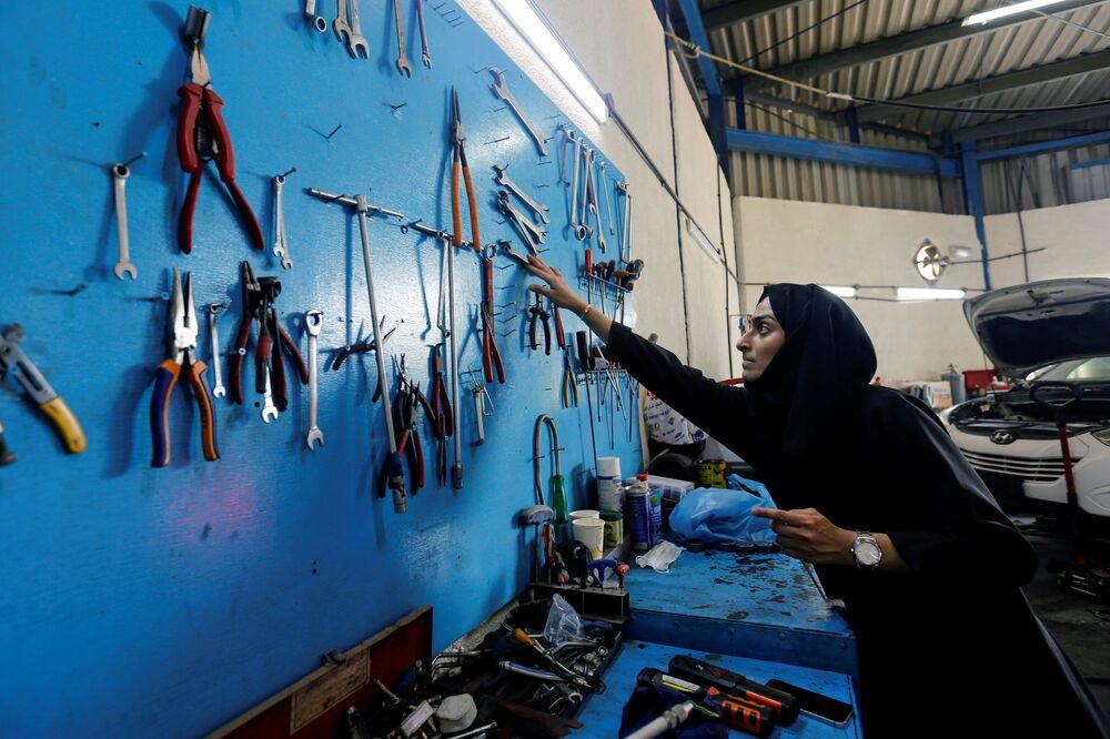 الإماراتية هدى المطروشي، 36 عاماً، تملك وتدير كراجاً لتصليح السيارات، تختار آلة تصليح في كراجها في الشارقة، الإمارات العربية المتحدة، 21 أبريل 2021