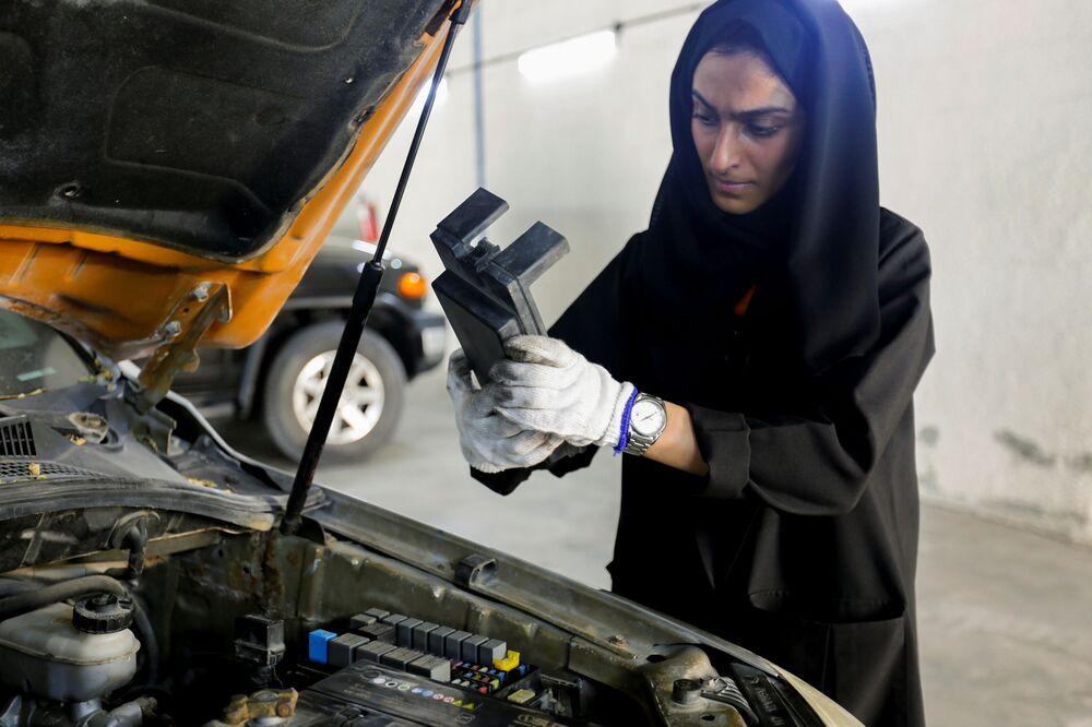 الإماراتية هدى المطروشي، 36 عاماً، تقوم بتصليح سيارة في كراجها في الشارقة، الإمارات العربية المتحدة، 21 أبريل 2021