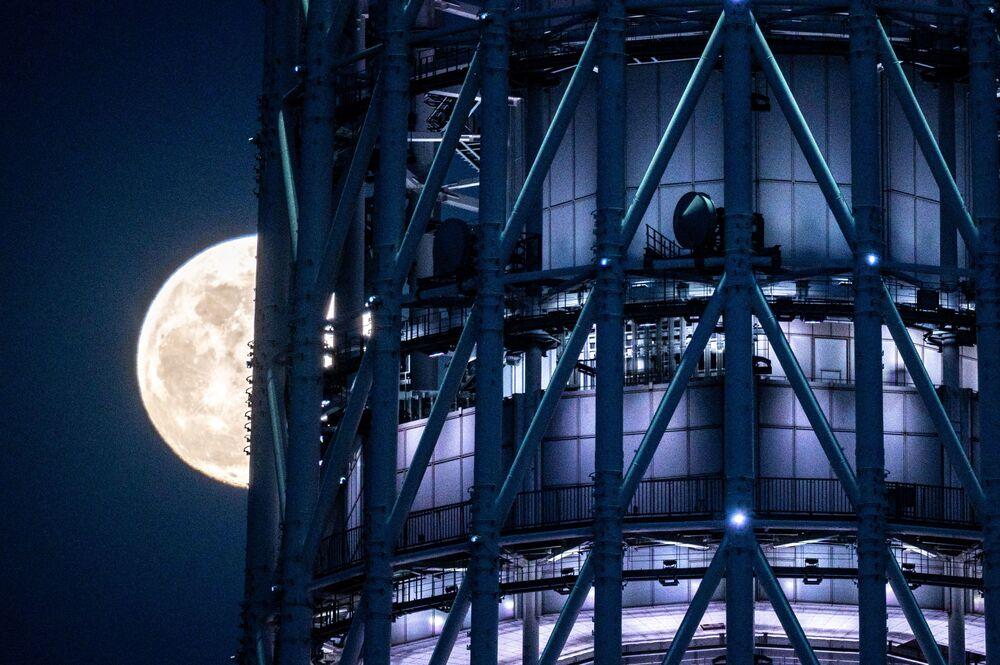 قمر عملاق على خلفية ناطحة سحاب في طوكيو، اليابان 26 أبريل 2021