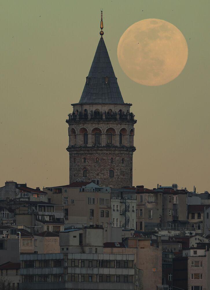قمر عملاق على خلفية برج غلطة (غالاتا تاور) بمنطقة غلاطة في اسطنبول، تركيا 26 أبريل 2021