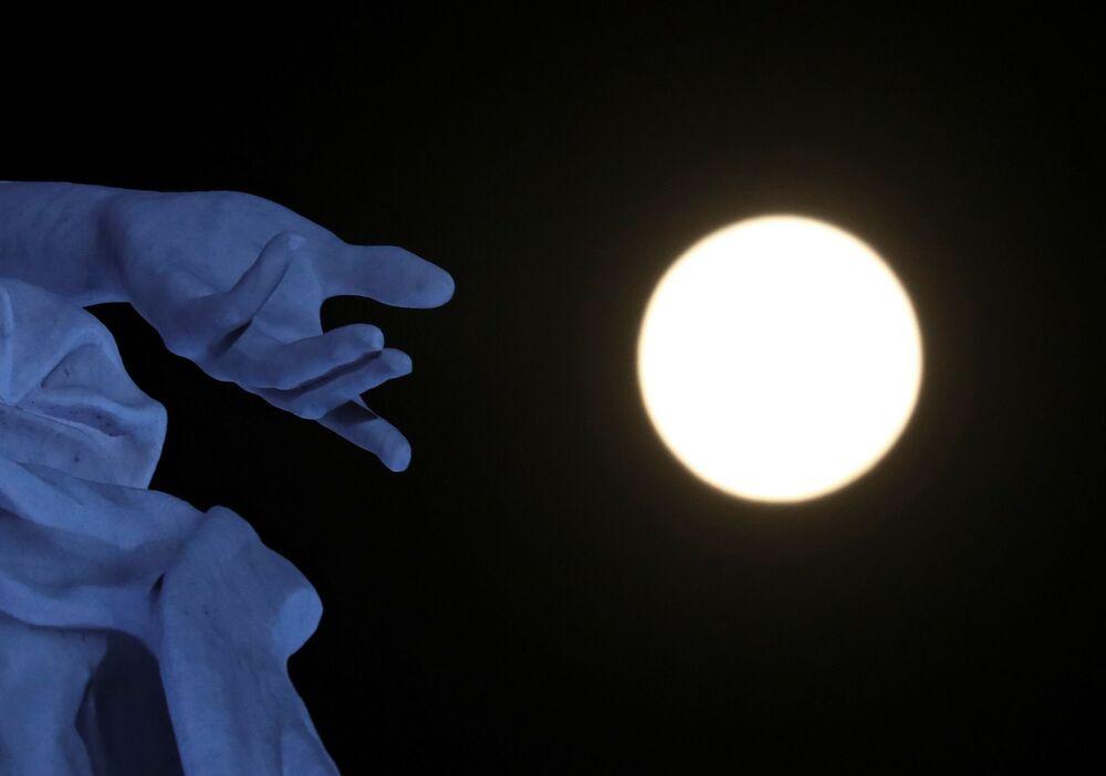قمر عملاق على خلفية تمثال كارتا ماينا ي لاس كوراتو ريجيونز أرجينتناس في بوينوس آيروس، الأرجنتين 26 أبريل 2021