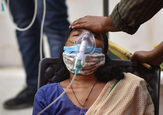كارثة إنسانية كبرى - تسجيل أرقام قياسية لحالات الإصابة بمرض كوفيد-19، كورونا، امرأة تعاني من ضيق التنفس في نيودلهي، الهند 28 أبريل 2021